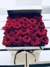 Czerwone żywe róże w kwadratowym białym boxie