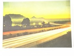 CAPE TOWN. CAR LIGHTS AT DUSK BELOW TABLE MOUNTAIN